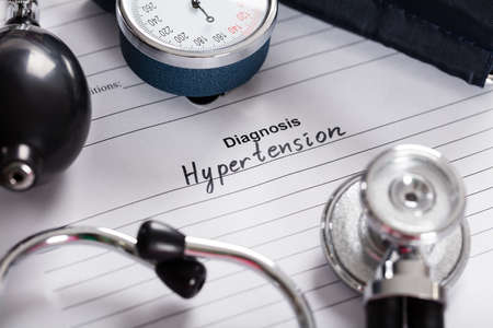 blood pressure gauge: Close-up Of Text Diagnosis Hypertension;Stethoscope And Blood Pressure Gauge On Medical Form Stock Photo