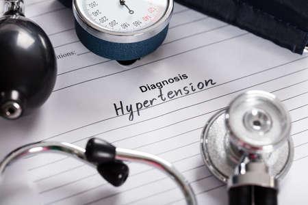 alto: Primer Del texto Diagnóstico hipertensión; Estetoscopio Y Indicador de presión sanguínea en el formulario médico