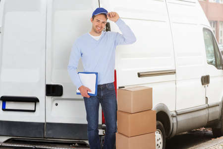 Portrait Of Confident Delivery Man With Parcels And Clipboard Against Truck photo