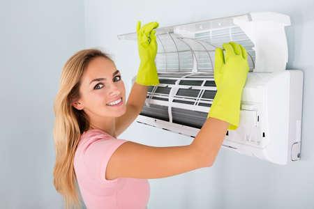 Jonge Vrouw Controleer En Schoonmaak Airconditioning Systeem Thuis