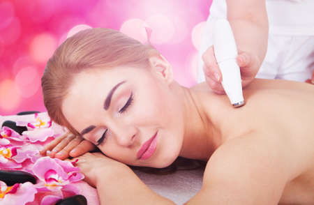 Relaxed Young Woman Receiving Microdermabrasion Therapy At Beauty Spa Stock Photo
