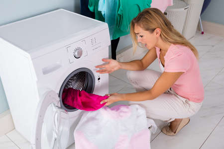 Shocked upset Young Woman Looking At Stained Bleached Cloth In Washing Machine At Laundry Room Stock Photo