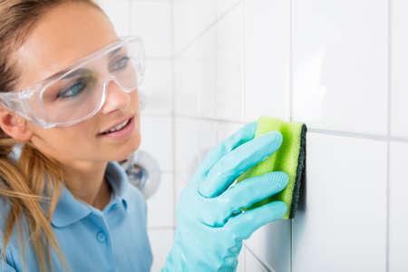 Jonge Vrouw met beschermende bril schoonmaken De witte tegels van de muur met behulp van Sponge