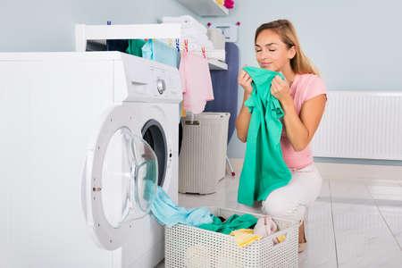Jonge glimlachende vrouw ruiken van kleding na het wassen in de wasmachine op Bijkeuken Stockfoto