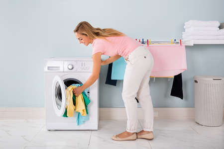 untidy: Smiling Woman Loading Untidy Clothes In Washing Machine In Utility Room