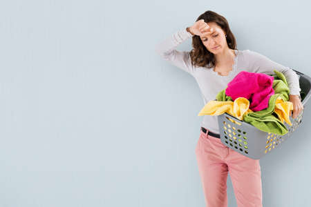 chores: Young Tired Woman Carrying Basket With Clothes On Colored Background Stock Photo