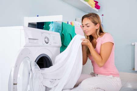 Jonge vrouw ruiken schone kleding in de buurt van de elektronische wasmachine in de wasruimte