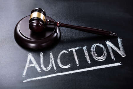 bidding: Close-up Of Auction Concept With Brown Gavel On Blackboard