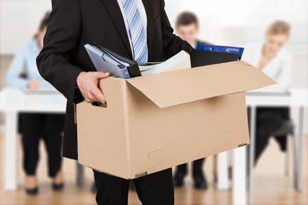 man carrying box: Close-up Of A Businessperson Carrying Cardboard Box During Office Meeting