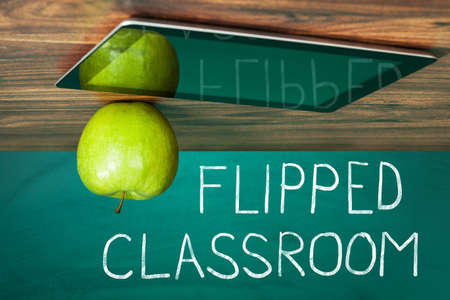 Flipped Classroom Concept On Blackboard With Apple And Digital Tablet On Wooden Table