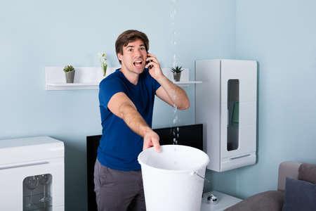 Worried Man Calling Plumber Bien que l'eau de fuite Falling Into Bucket At Home Banque d'images - 70824504