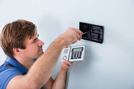 technician: Young Male Technician Installing Security System Using Screwdriver