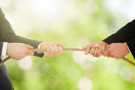 Close-up Of A Two Businessman Pulling Rope In Opposite Direction Stock Photo