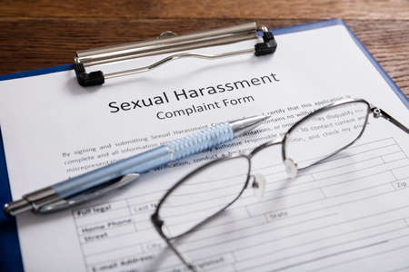 Close-up Of Sexual Harassment Complaint Form With Pen At Desk Stock Photo