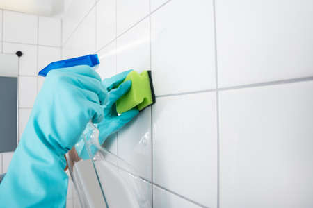 Cleaning Service Professional Wearing Gloves Cleaning The Tiled Wall Using Sponge And Spray Bottle