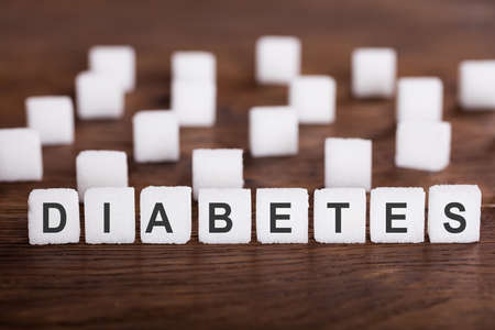 sweeten: Diabetes Text On Sugar Cubes On Wooden Desk Stock Photo