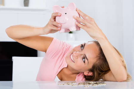 Young Happy Woman Emptying Her Piggybank Savings With Less Than Expected At Home Stock Photo