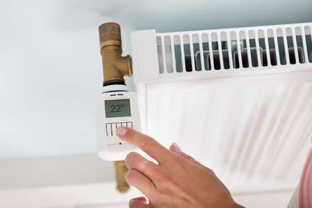 Close-up Of A Persons Hand Adjusting Temperature To Reduce Heat On Digital Thermostat Stock Photo