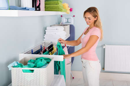 Woman Hanging Wet Clean Cloth On Clothes Line At Laundry Room