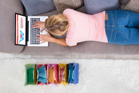 woman laying: High Angle View Of Young Woman Lying On Sofa Using Laptop For Online Shopping