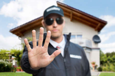 Close-up Of A Young Male Security Guard Making Stop Gesture In Front Of A House Banco de Imagens