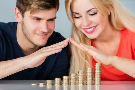 Close-up Of Young Couple Saving Money And Managing Finances