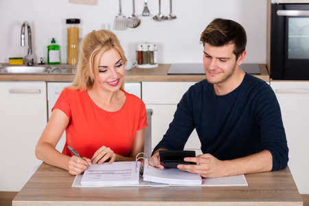 managing money: Couple Calculating Family Money Budget And Invoices For Insurance And Tax Using Calculator At Home Stock Photo