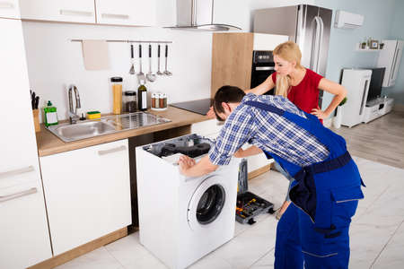 machines: Woman Looking At Young Male Worker With Toolbox Repairing Washing Machine In Kitchen Room Stock Photo