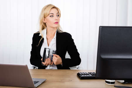 Businesswoman Stealing A Calculator From Office Desk