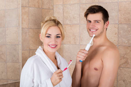 Portrait Of Young Smiling Couple With Brushing Teeth In Bathroom