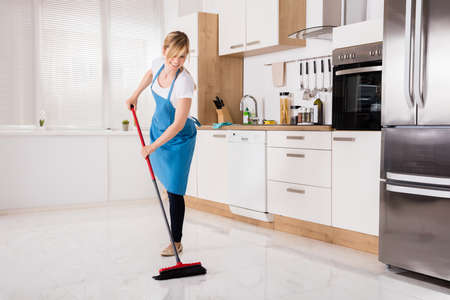 Jonge Housemaid Cleaning Floor Met Broom In Kitchen Stockfoto