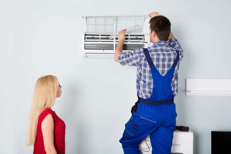 Woman Looking At Young Male Technician Repairing AC At Home