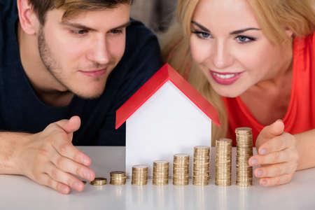 incremento: Joven pareja sonriente Proteger modelo de casa con monedas apiladas en el escritorio. Inmobiliaria Concepto Crecimiento Renta