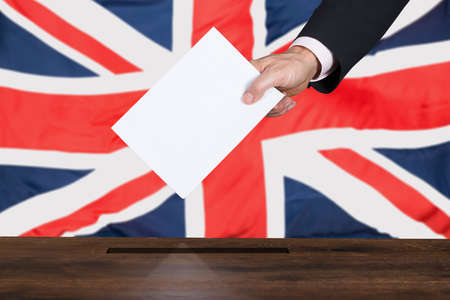 parliamentary: Businessperson Hand Putting Vote Into Ballot Box In Front Of United Kingdom Flag Stock Photo