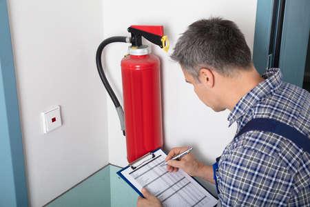 Close-up de um profissional masculino que verific um extintor de incêndio usando a prancheta Imagens