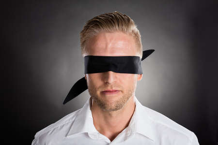 Young Lost Businessman With A Black Blindfold Stock Photo