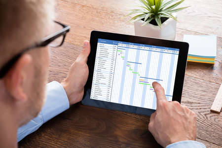 Businessman Working On Gantt Chart On Digital Tablet At Wooden Desk