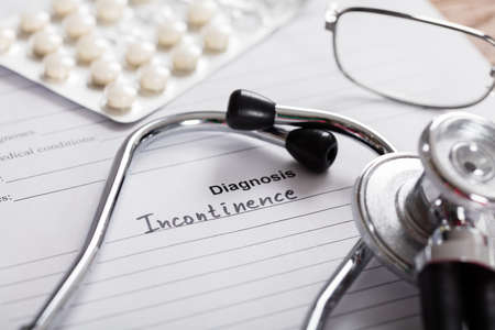 constipation symptom: Close-up Of Diagnosis Incontinence Word And Medical Composition On Paper