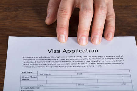 visa approved: High Angle View Of Person Hand On Visa Application Form At Wooden Desk