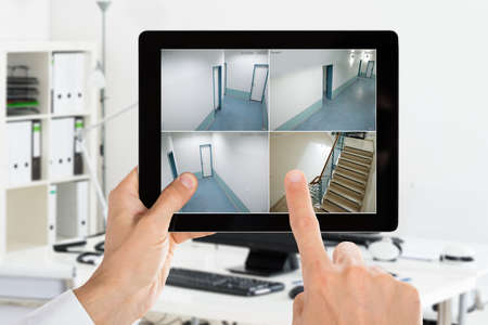 남자 사무실에서 디지털 태블릿에 카메라 CCTV 보안 비디오 모니터링