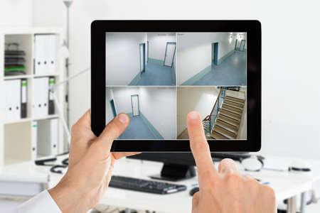 Hombre de vigilancia de la cámara de seguridad CCTV Videos en la tableta digital en la Oficina