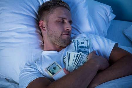 통화 메모의 번들로 침대에서 잠자는 남자
