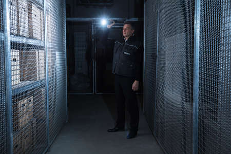 building security: Rear View Of A Security Guard Standing In The Warehouse Holding Flashlight
