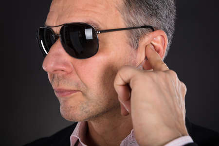 earpiece: Close-up Of A Male Security Guard Listening To Earpiece On Gray Background Stock Photo