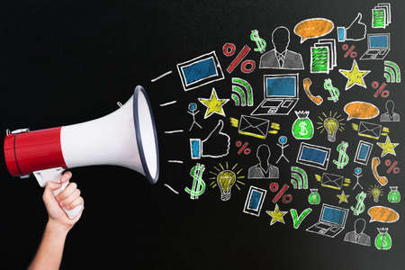 greenboard: Hand Holding Megaphone With Different Icons For Digital Marketing Concept On Blackboard