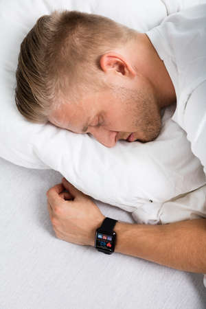resting heart rate: Man Sleeping With Smart Watch In His Hand Showing Heartbeat Rate