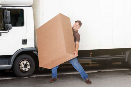 removal van: A Delivery Man Or Mover Holding Heavy Box In Front Of The Van