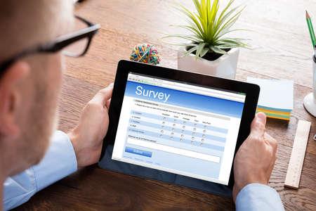 persona leyendo: Person Filling Online Survey Form On Digital Tablet At Wooden Desk Foto de archivo