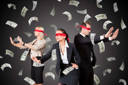 ojos vendados: A Blindfolded Business People Standing In Money Rain On Gray Background Foto de archivo
