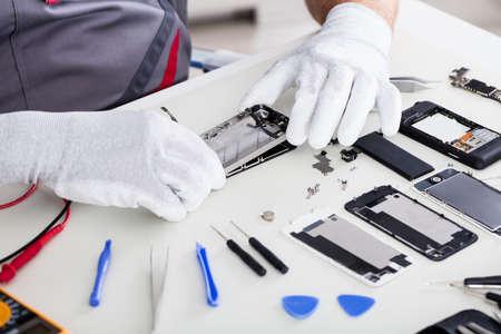 Nahaufnahme einer Techniker-Hand, die Handy repariert